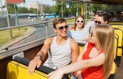 Grupo de amigos sonrientes que viajan en bus turístico Imagen de archivo libre de regalías