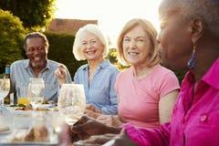 Grupo de amigos superiores que apreciam o partido de jantar exterior em casa foto de stock