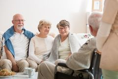 Grupo de amigos superiores que sentam-se junto na sala de visitas comum do lar de idosos foto de stock