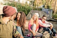 Grupo de amigos urbanos que têm o divertimento para fora no parque do bmx do patim imagem de stock royalty free