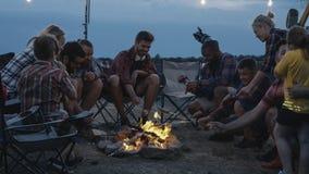 Grupo de amigos de viagem que fritam salsichas no acampamento fotografia de stock