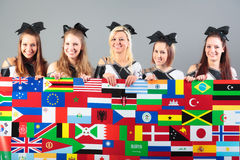 Grupo de animadoras que sostienen el cartel con las banderas Foto de archivo