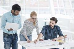 Grupo de arquitectos que discuten planes en oficina moderna imagen de archivo
