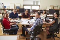 Grupo de arquitectos que se encuentran alrededor del escritorio foto de archivo libre de regalías