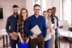 Grupo de arquitetos novos bem sucedidos que levantam no escritório imagem de stock royalty free