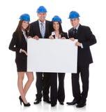 Grupo de arquitetos que guardam o cartaz Fotografia de Stock Royalty Free