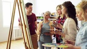 Grupo de artistas que discutem que pinta na escola de arte video estoque