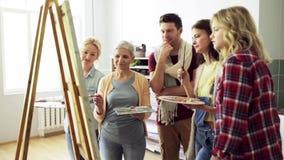 Grupo de artistas que discutem que pinta na escola de arte vídeos de arquivo
