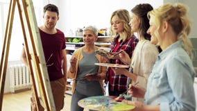 Grupo de artistas que discuten que pinta en la escuela de arte metrajes