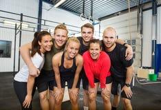 Grupo de atletas felices que se colocan en la aptitud cruzada Imágenes de archivo libres de regalías