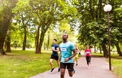 Grupo de atletas jovenes que corren en parque soleado verde Fotos de archivo libres de regalías