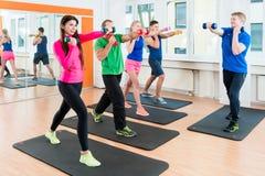 Grupo de atletas no gym que faz a ginástica com pesos imagem de stock royalty free