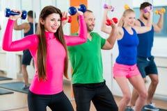 Grupo de atletas no gym que faz a ginástica com pesos imagens de stock