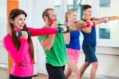 Grupo de atletas no gym que faz a ginástica com pesos foto de stock royalty free