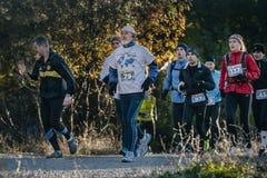Grupo de atletas que corren abajo del camino en bosque del otoño Imagen de archivo