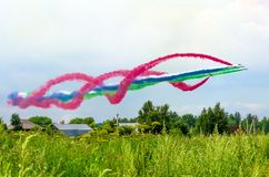 Grupo de avião do avião de combate com um traço de fumo colorido contra o céu Fotografia de Stock