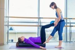 Grupo de ayuda de las mujeres del instructor personal de Pilates de los aeróbicos en una clase del gimnasio Imágenes de archivo libres de regalías