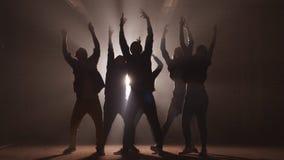 Grupo de bailarines de la calle que realizan diversos movimientos en la calle oscura almacen de metraje de vídeo