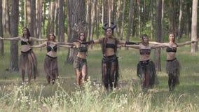 Grupo de bailarines de las mujeres con maquillaje y en los trajes fabulosos místicos que bailan danza maravillosa en humo del col almacen de video