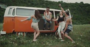 Grupo de baile joven de los amigos feliz en la naturaleza, dentro de la furgoneta retra y en la hierba metrajes