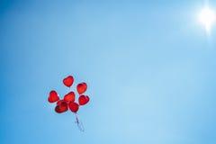 Grupo de balões vermelhos do grupo em um céu azul Fotografia de Stock Royalty Free