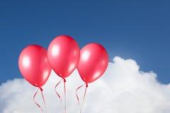 Grupo de balões vermelhos festivos no fundo do céu azul Fotos de Stock