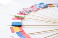 Grupo de bandeiras de papel diminutas de diversos países: Grécia, Alemanha, Suécia, Noruega, Inglaterra, Itália, França, Espanha, fotos de stock royalty free