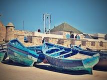 Grupo de barcos de pesca azules en la orilla en el embarcadero en la ciudad de Essaouira Marruecos imagenes de archivo