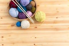 Grupo de bolas e de agulhas coloridas do fio na placa da palha Imagem de Stock