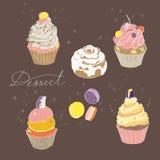 Grupo de bolos coloridos em um fundo do marrom escuro Vetor Imagens de Stock Royalty Free
