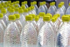 Grupo de botellas plásticas con el soporte del agua en fila Fotos de archivo