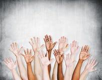 Grupo de braços humanos aumentados com muro de cimento Imagem de Stock