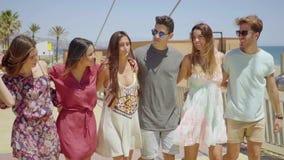 Grupo de brazo que camina de los amigos jovenes de moda en brazo