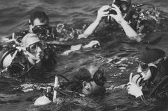 Grupo de buceadores que bucean que nadan en el mar Foto de archivo libre de regalías