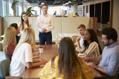 Grupo de And Businesswoman Addressing do homem de negócios de candidatos novos que sentam-se em torno da tabela foto de stock