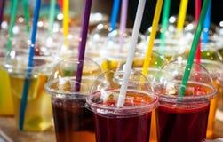 Grupo de cócteles coloreados en tazas plásticas Imagen de archivo