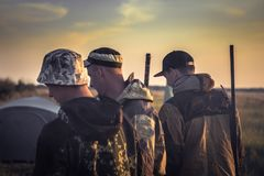 Grupo de caçadores afastado girados dos homens que preparam-se para caçar durante a época de caça fotos de stock