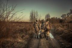 Grupo de caçadores dos homens com equipamento da caça que andam no por do sol da época de caça da estrada secundária fotos de stock