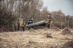 Grupo de caçadores dos homens na camuflagem com o barco de borracha que cruza o campo rural seco com os arbustos no fundo durante fotografia de stock