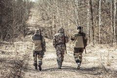 Grupo de caçadores dos homens que parte na estrada rural durante a época de caça imagens de stock