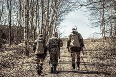 Grupo de caçadores dos homens que vão acima na estrada rural durante a época de caça fotografia de stock