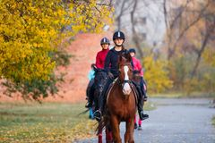 Grupo de caballo de montar a caballo de los adolescentes en parque del otoño Imagen de archivo libre de regalías