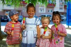 Grupo de cabritos felices que comen el helado de la fruta Foto de archivo libre de regalías