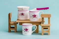 Grupo de café colorido decorativo da porcelana no fundo azul fotos de stock royalty free