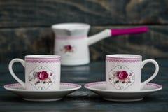 Grupo de café colorido decorativo da porcelana no fundo de madeira imagens de stock royalty free