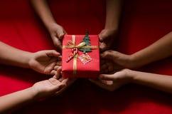 Grupo de caja de regalo de la Navidad del control de los niños de la mano en fondo rojo Imagen de archivo libre de regalías