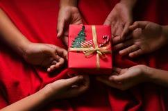 Grupo de caja de regalo de la Navidad del control de los niños de la mano en fondo rojo Imagen de archivo