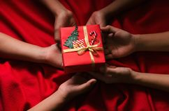 Grupo de caja de regalo de la Navidad del control de los niños de la mano en fondo rojo Imagenes de archivo