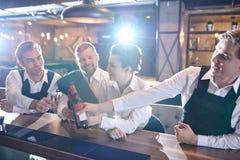 Grupo de camareros que celebran éxito después de horas en restaurante imagen de archivo