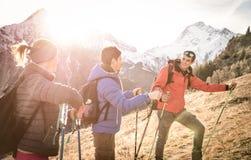 Grupo de caminantes de los amigos que emigran en las montañas francesas en la puesta del sol Foto de archivo
